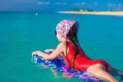 Little adorable girl on a surfboard in the turquoise sea Royalty Free Stock Image