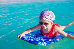 Little adorable girl on a surfboard in the turquoise sea Royalty Free Stock Photography