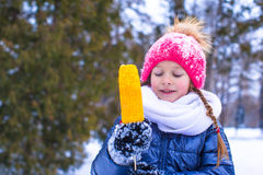 Little adorable girl with sweet corn at winter Royalty Free Stock Photos