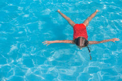 Little adorable girl swimming in the swimmingpool Stock Photo