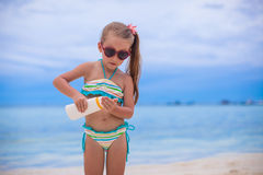 Little adorable girl in swimsuit holds suntan Royalty Free Stock Photos