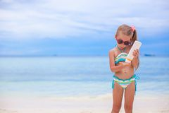 Little adorable girl in swimsuit holds suntan Royalty Free Stock Photography