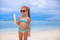 Little adorable girl in swimsuit holds suntan Stock Photos