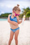 Little adorable girl in swimsuit rubs sunscreen Stock Photography