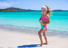 Little adorable girl in swimsuit with suntan. Little adorable girl in swimsuit holds suntan lotion bottle Stock Photography