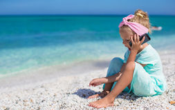 Little adorable girl talking at phone during beach Stock Images