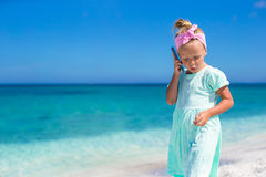 Little adorable girl talking at phone during beach Stock Image