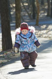 Little adorable girl toddling without help in cold weather park Stock Photo