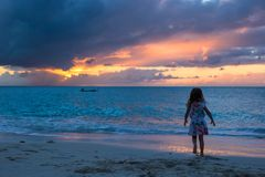 Little adorable girl walking in the sunset on a tropical beach Stock Photography
