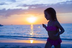 Little adorable girl walking in the sunset on a Royalty Free Stock Photo