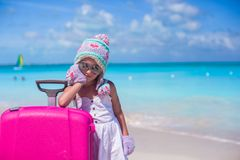 Little adorable girl in warm winter hat and mittens on a tropical beach Stock Image