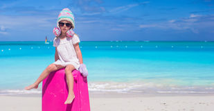 Little adorable girl in warm winter hat and mittens on tropical beach Stock Images