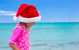 Little adorable girl wearing Santa hat at tropical Royalty Free Stock Image