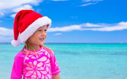 Little adorable girl wearing Santa hat at tropical Stock Image