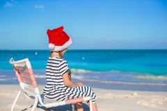 Little adorable girl wearing Santa hat at tropical Stock Photos