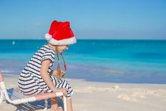 Little adorable girl wearing Santa hat at tropical Stock Photos