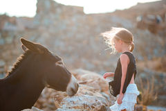 Little adorable girl with wild donkey on greek island outdoors Stock Images