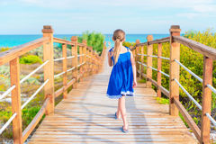 Little adorable girl on a wooden bridge on their way to a white tropical beach and turquoise ocean Royalty Free Stock Photo