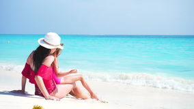 Little adorable girl and young mother at tropical beach enjoy their sea vacation stock footage