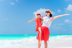 Little adorable girl and young mother at tropical beach. Family of two have a lot of fun during summer vacation Stock Photo