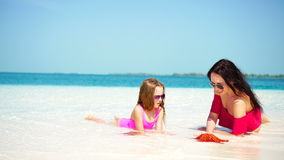 Little adorable girl and young mother at tropical beach lying on white beach and enjoy their summer vacation stock footage