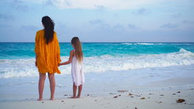 Little adorable girl and young mother at tropical beach in warm evening stock footage