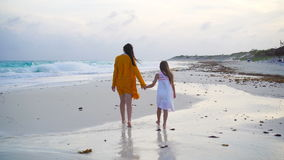 Little adorable girl and young mother at tropical beach in warm evening stock video footage