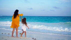 Little adorable girl and young mother at tropical beach in warm evening. Little girl dancing on the seashore at sunset stock footage