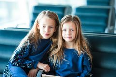 Little adorable girls in airport waiting for boarding near big window. Adorable little girl in airport with her luggage Royalty Free Stock Image