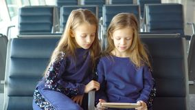 Little adorable girls in airport waiting for boarding playing with laptop stock footage