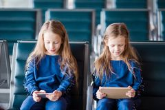 Little adorable girls in airport waiting for boarding playing with laptop. Adorable little girls in airport with her luggage Royalty Free Stock Images