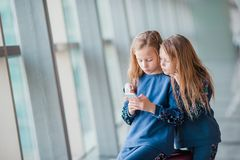 Little adorable girls in airport waiting for boarding and playing with laptop. Little adorable girls in airport near big window with their laptop Royalty Free Stock Photo
