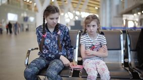 Two sisters at the airport. Little girl upset with her sister because tablet. Little adorable girls in airport waiting for boarding playing with laptop stock video footage