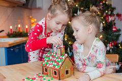 Little adorable girls decorating gingerbread house Stock Photo
