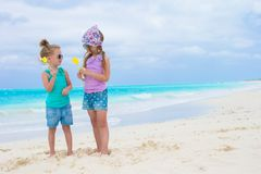 Little adorable girls with eggs on white tropical beach Stock Images