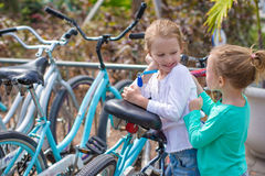 Little adorable girls having fun near the bikes on. Little adorable girls having fun near the bikes Royalty Free Stock Images