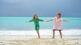 Little adorable girls having fun at tropical beach playing together. Little girls having fun at tropical beach playing together at shallow water stock footage