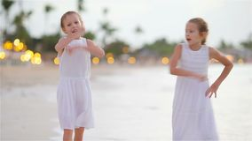 Little adorable girls having fun at tropical beach playing together. Little girls having fun at tropical beach playing together at shallow water stock video footage