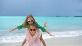 Little adorable girls having fun at tropical beach playing together. SLOW MOTION. Little girls having fun at tropical beach playing together at shallow water stock video