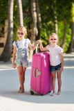 Little adorable girls with luggage during summer Royalty Free Stock Images