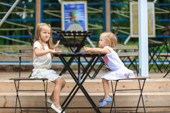 Little adorable girls at outdoor cafe on warm Stock Images