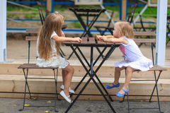 Little adorable girls at outdoor cafe on warm Stock Photography