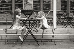 Little adorable girls at outdoor cafe on warm Royalty Free Stock Photography