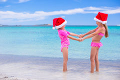 Little adorable girls in red Santa hats on beach Stock Images