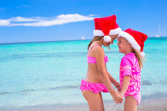Little adorable girls in red Santa hats on beach Royalty Free Stock Photography