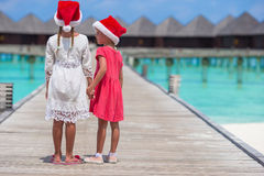 Little adorable girls in red Santa hats on beach Royalty Free Stock Image