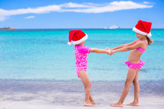 Little adorable girls in red Santa hats on beach Stock Photos