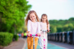 Little adorable girls riding on scooters in park outdoors. Two little girls riding on scooter in the park outdoor Royalty Free Stock Images