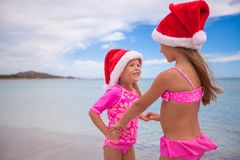 Little adorable girls in Santa hats during beach Stock Photography