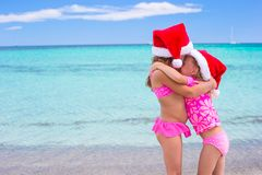 Little adorable girls in Santa hats during beach Royalty Free Stock Images